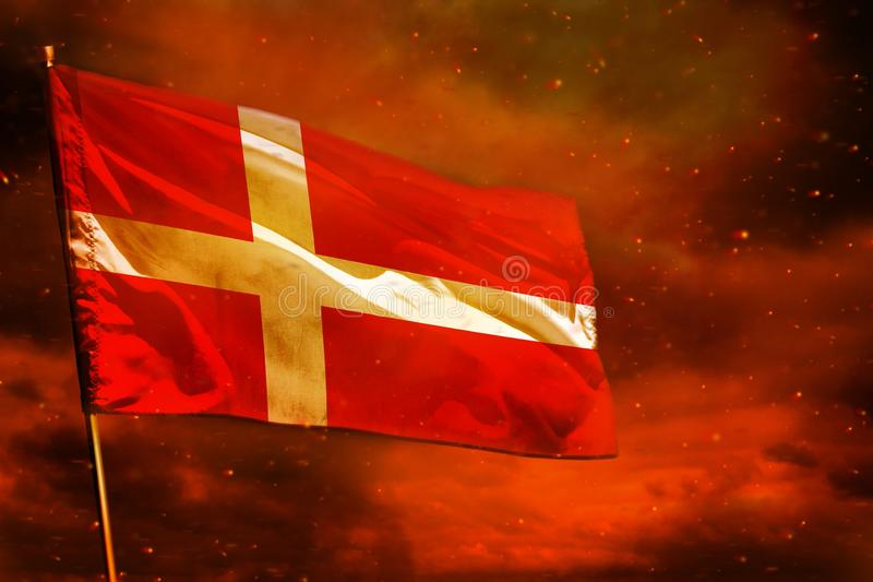 Fluttering Denmark flag on crimson red sky with smoke pillars background. Troubles concept. Fluttering Denmark flag on crimson red sky with smoke pillars royalty free stock image