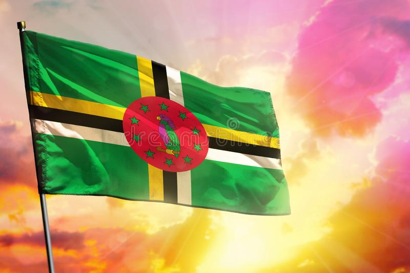 Fluttering Dominica flag on beautiful colorful sunset or sunrise background. Success concept royalty free stock photos