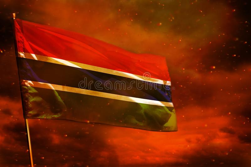 Fluttering Gambia flag on crimson red sky with smoke pillars background. Troubles concept. Fluttering Gambia flag on crimson red sky with smoke pillars royalty free stock images