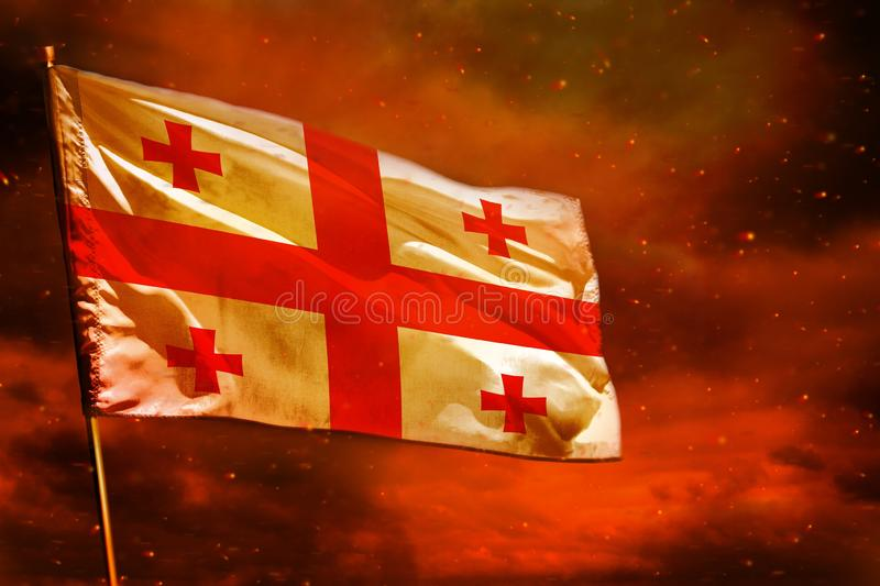 Fluttering Georgia flag on crimson red sky with smoke pillars background. Troubles concept. Fluttering Georgia flag on crimson red sky with smoke pillars stock photography