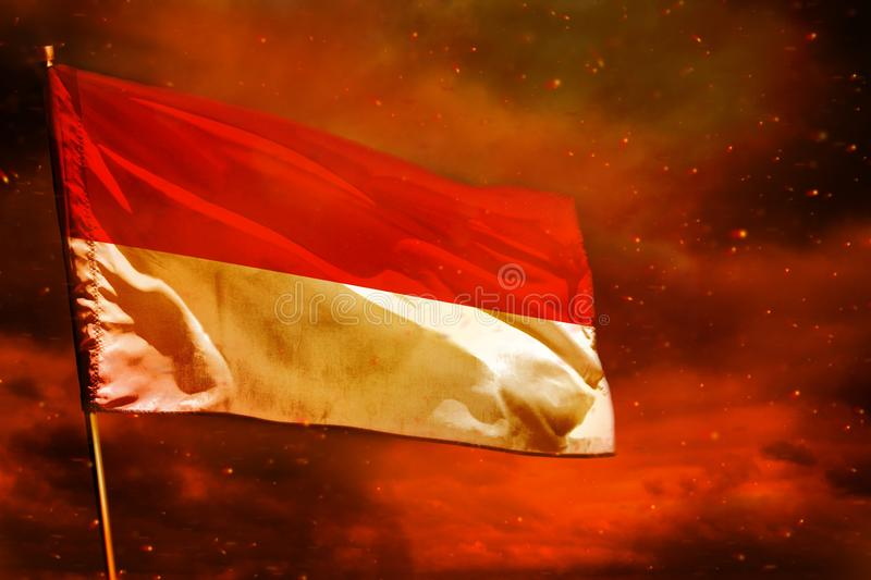 Fluttering Indonesia flag on crimson red sky with smoke pillars background. Troubles concept. Fluttering Indonesia flag on crimson red sky with smoke pillars royalty free stock images