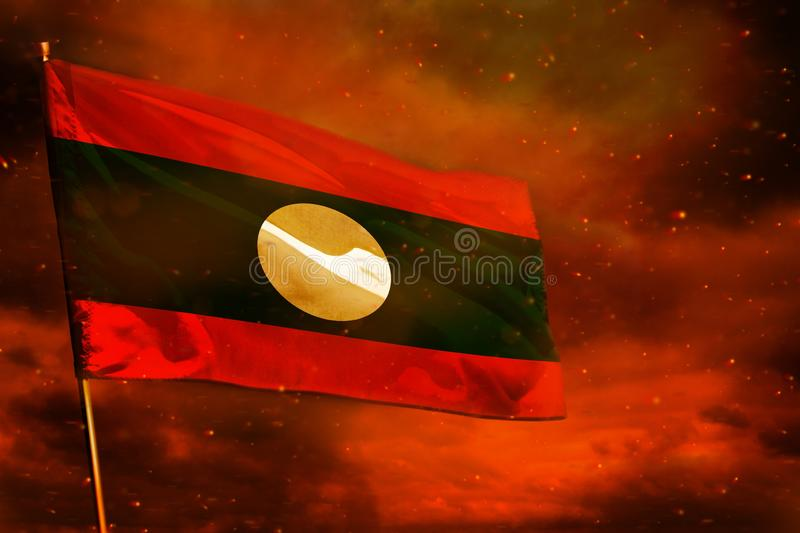 Fluttering Lao People Democratic Republic flag on crimson red sky with smoke pillars background. Troubles concept. Fluttering Lao People Democratic Republic flag stock photography