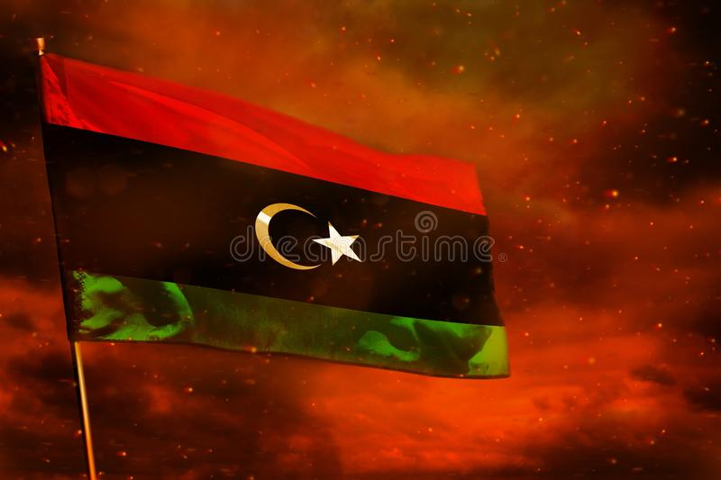 Fluttering Libya flag on crimson red sky with smoke pillars background. Troubles concept. Fluttering Libya flag on crimson red sky with smoke pillars background royalty free stock image