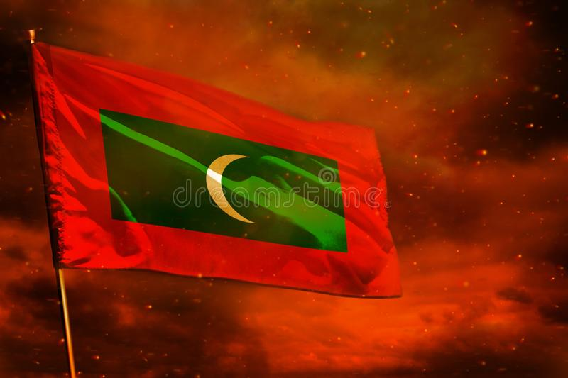Fluttering Maldives flag on crimson red sky with smoke pillars background. Troubles concept. Fluttering Maldives flag on crimson red sky with smoke pillars royalty free stock photography
