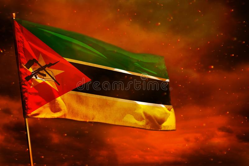 Fluttering Mozambique flag on crimson red sky with smoke pillars background. Troubles concept. Fluttering Mozambique flag on crimson red sky with smoke pillars royalty free stock images