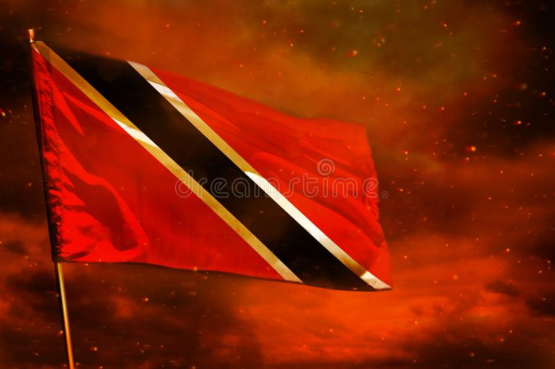 Fluttering Trinidad and Tobago flag on crimson red sky with smoke pillars background. Troubles concept. Fluttering Trinidad and Tobago flag on crimson red sky royalty free stock photo