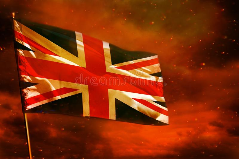 Fluttering United Kingdom UK flag on crimson red sky with smoke pillars background. Troubles concept. Fluttering United Kingdom UK flag on crimson red sky with royalty free stock photography