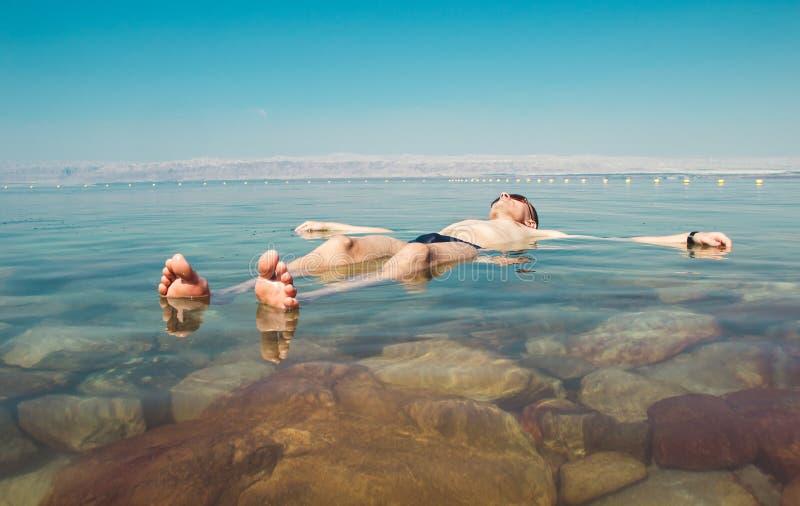Flutuador do homem que medita no Mar Morto da água Recreação do turismo, conceito saudável do estilo de vida Copie o espaço Medit imagem de stock