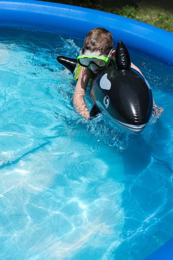 Flutuador novo da equitação do menino na associação imagem de stock