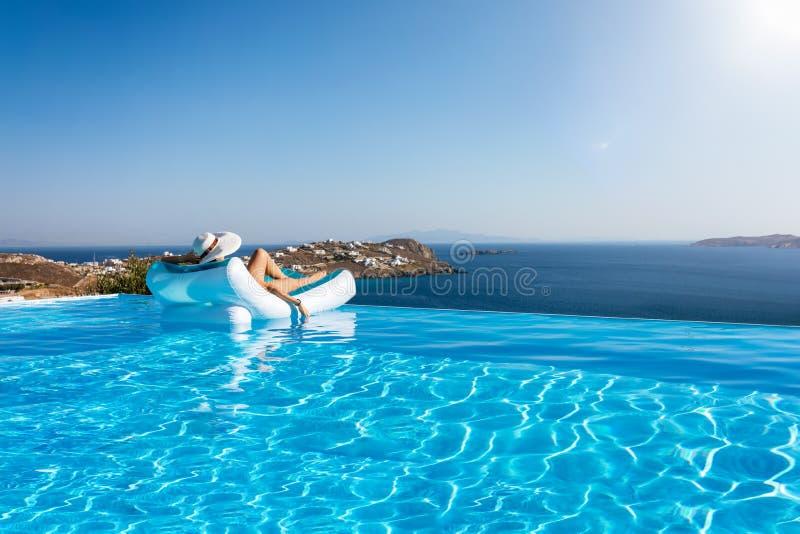 Flutuadores da mulher em uma piscina da infinidade com vista ao mar Mediterrâneo em Grécia foto de stock