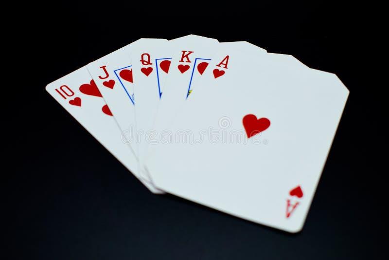 Flux droit de quinte royale des cartes de coeurs en jeu de poker sur le fond noir image stock