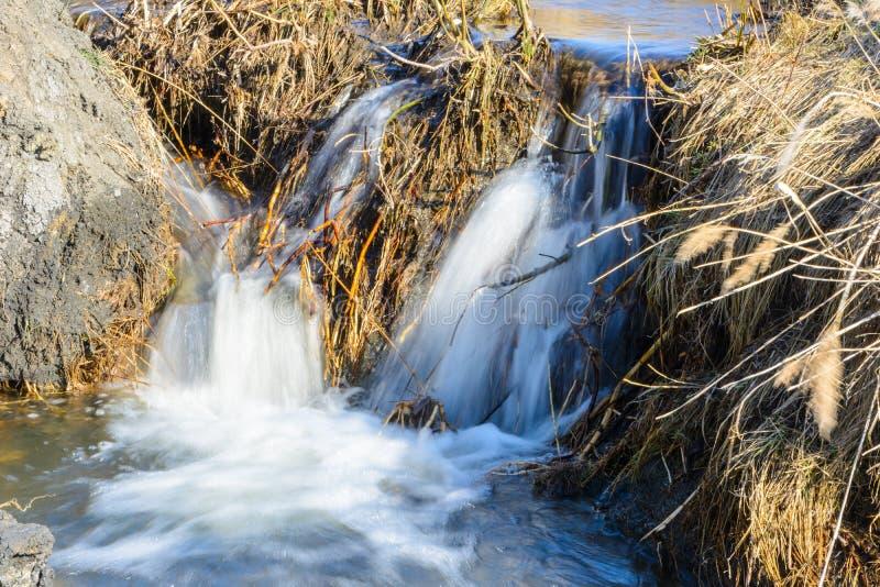 Fluxo esperado desde há muito tempo das angras da mola sobre ravinas e montes em um dia ensolarado Corredeira da água e cachoeira fotos de stock royalty free