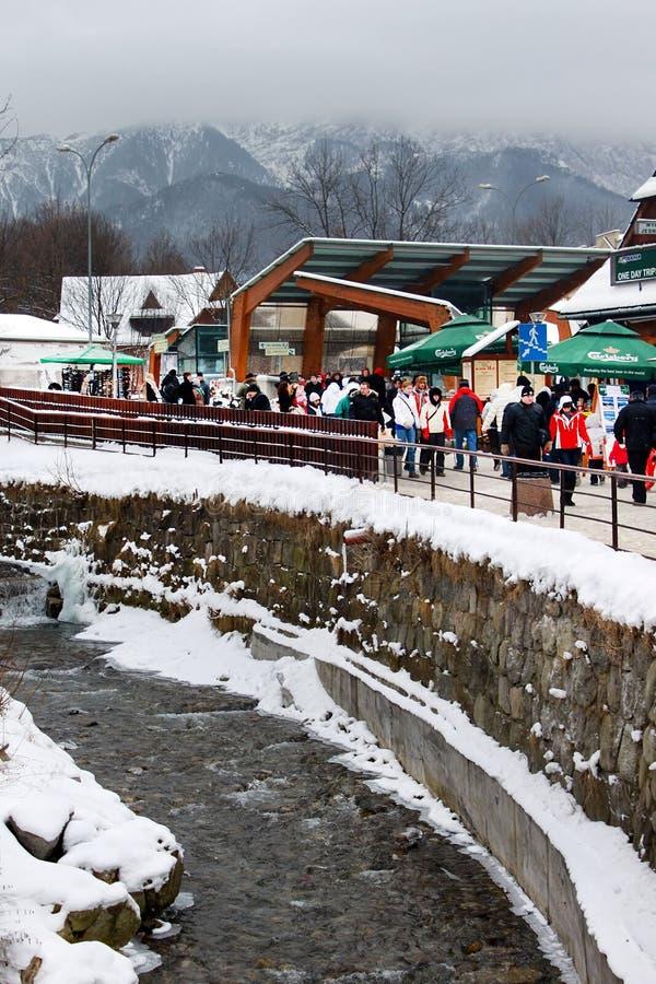 Fluxos de córrego da montanha entre casas de cortiço velhas e arquitetura moderna na estação no inverno, Zakopane do highe fotos de stock royalty free