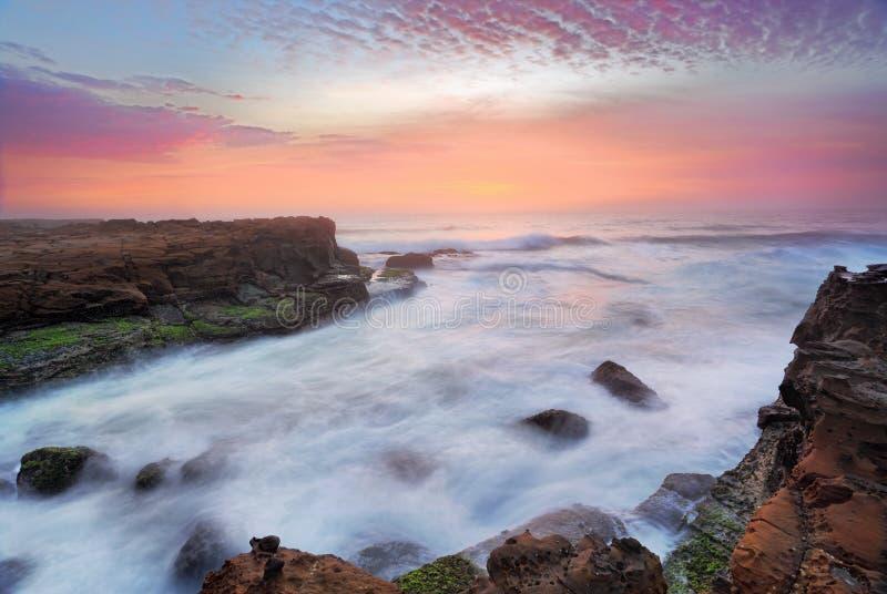 Fluxos impressionantes do nascer do sol e do oceano sobre rochas maré imagem de stock