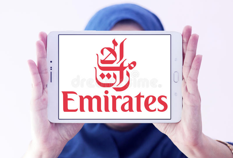 Fly emirates logo. Logo of fly emirates on samsung tablet holded by arab muslim woman stock photo