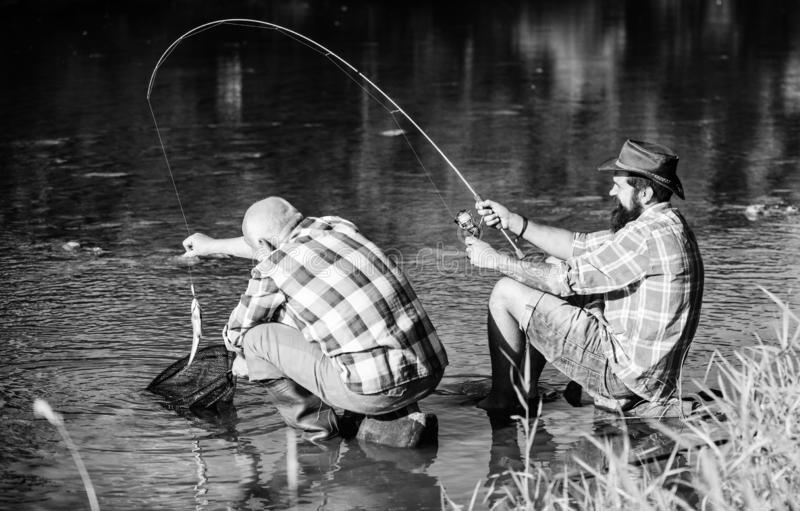 Fly fish hobby of men. retirement fishery. retired father and mature bearded son. Two male friends fishing together stock photo
