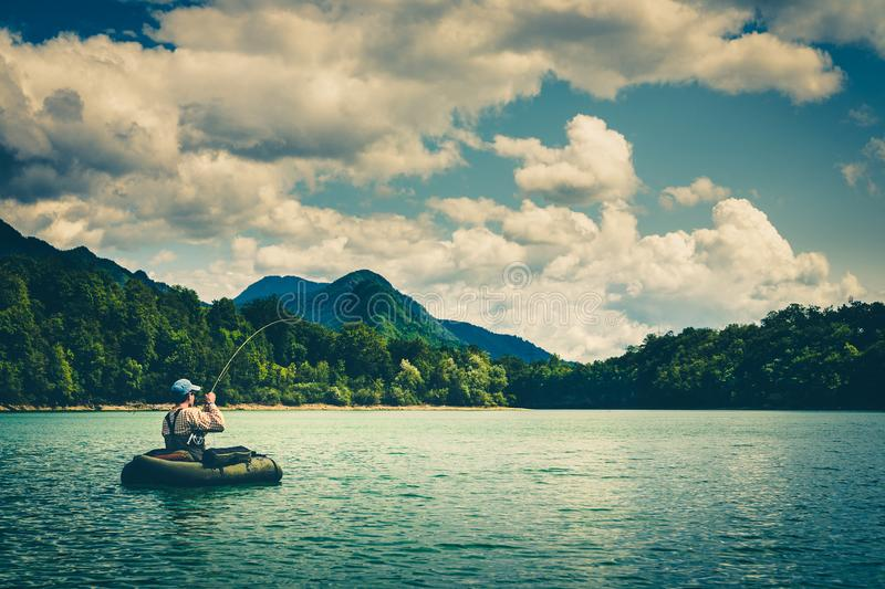 Fly fisherman on bellyboat fighting with big trout, Slovenia. Fisherman sitting in bellyboat and fighting with big trout on lake in Jesenice, Slovenia. Still royalty free stock image