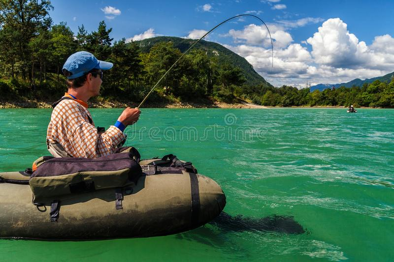 Fly fisherman on bellyboat fighting with big trout, Slovenia. Fisherman sitting in bellyboat and fighting with big trout on lake in Jesenice, Slovenia. Still stock photo
