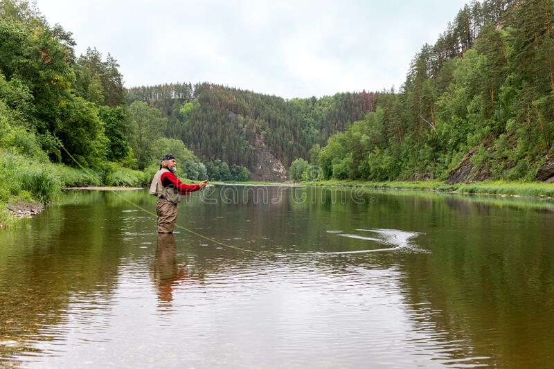 Fly fisherman catching a trout. Outdoor fishing in river. Fisherman fishing equipment royalty free stock photography
