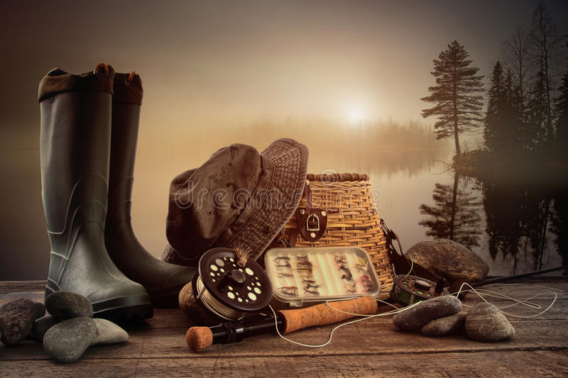 Fly fishing equipment on deck with misty lake royalty free stock photo