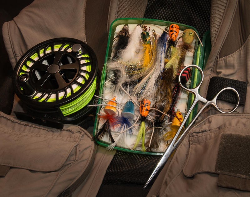 Fly fishing equipment tableau. Still life with fly fishing gear including a fly reel, assorted flies, fishing vest and forceps royalty free stock image