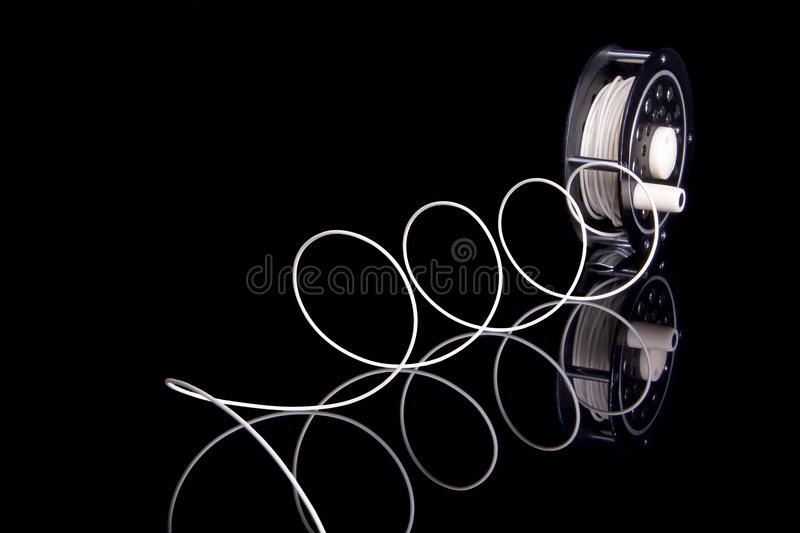 Fly Fishing Reel. Old fly fishing reel on black. The line is spiraling off of the reel and is captured in the clearly visible reflection royalty free stock photos