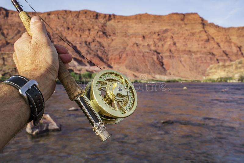 Fly Fishing reel and rod with river and red rock background stock photography