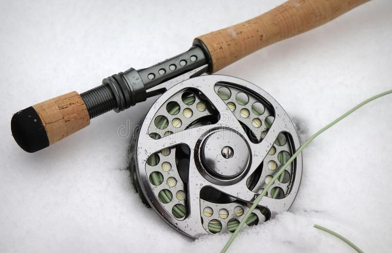 Fly fishing rod and reel in the snow royalty free stock photography
