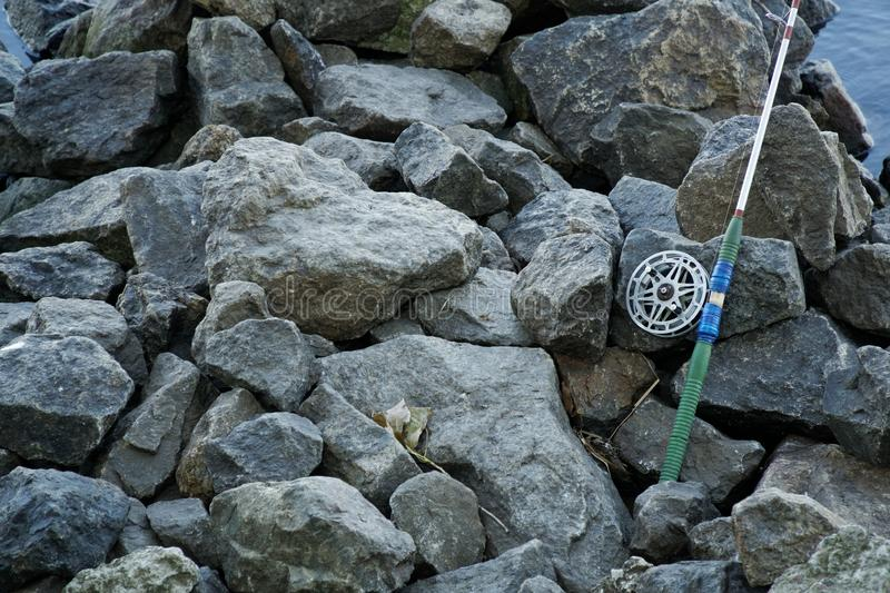 Fly fishing rod and reel on stone river bank. Fishing scene on the banks.  stock photos