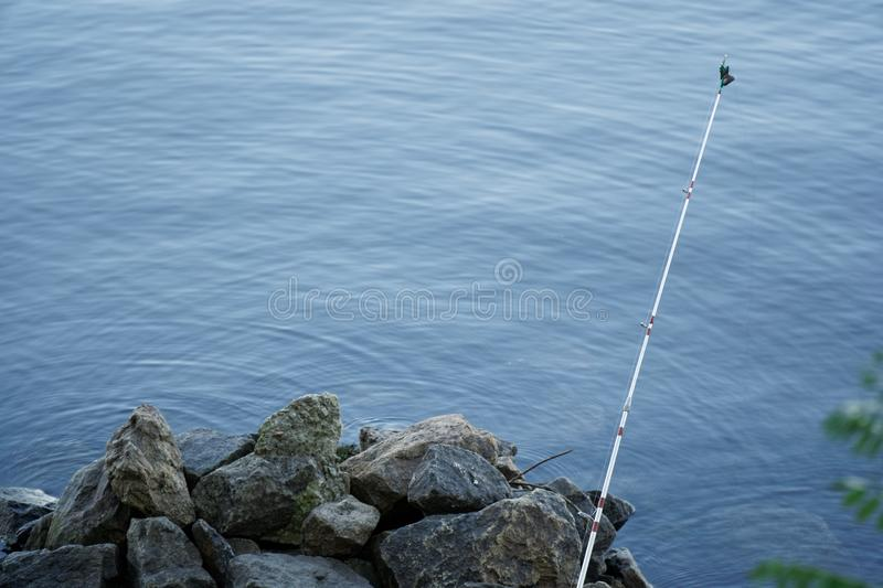 Fly fishing rod and reel on stone river bank. Fishing scene on the banks.  royalty free stock image