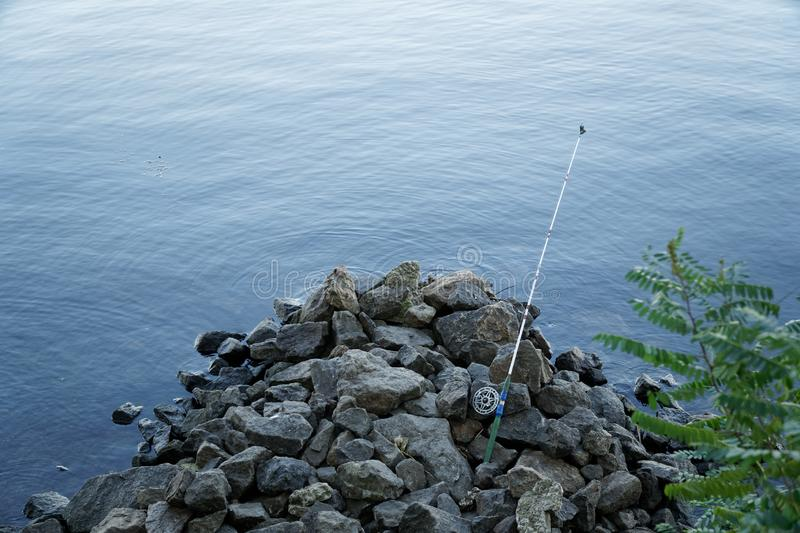 Fly fishing rod and reel on stone river bank. Fishing scene on the banks.  royalty free stock photography