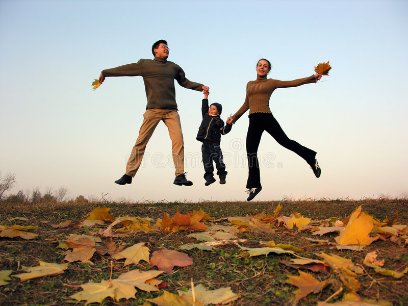 Fly happy family with autumn leaves. Sundown