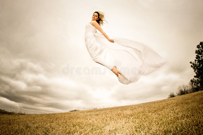 Fly happy woman2. Runaway bride in the field during a stormy windy day royalty free stock photography