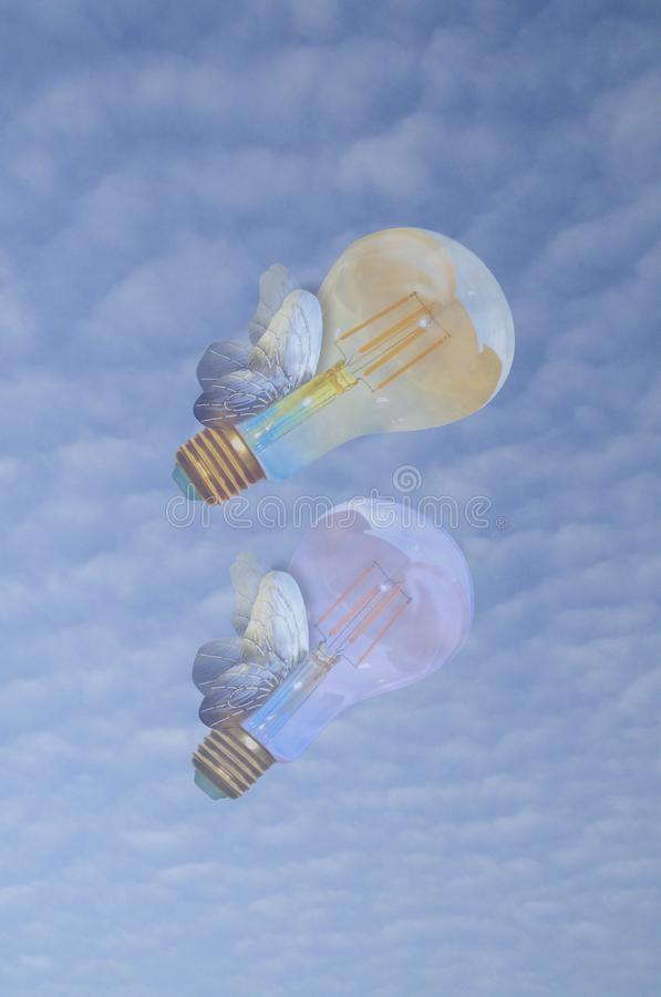 Fly high.Edison Lightbulbs flying with their wings on the sky. Two lightbulbs flying with wings like butterflies on blue sky with Beautiful Clouds in background stock photography