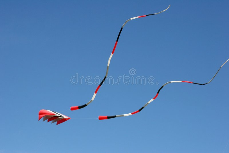 Fly a Kite. A stunt kite flying high in the blue sky stock image