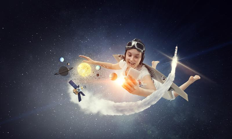 Fly with self-made plane wing. Joyful girl flying with self-made paper wing in the sky, making selfie, with planets and satellites, dark space background stock image