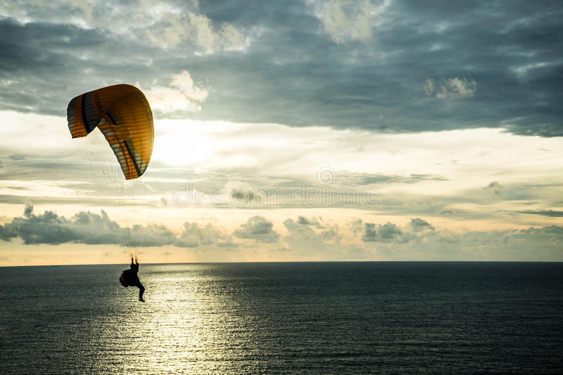 Fly on the sky by parachuting. Flying is in the sky by parachuting at sunset stock images