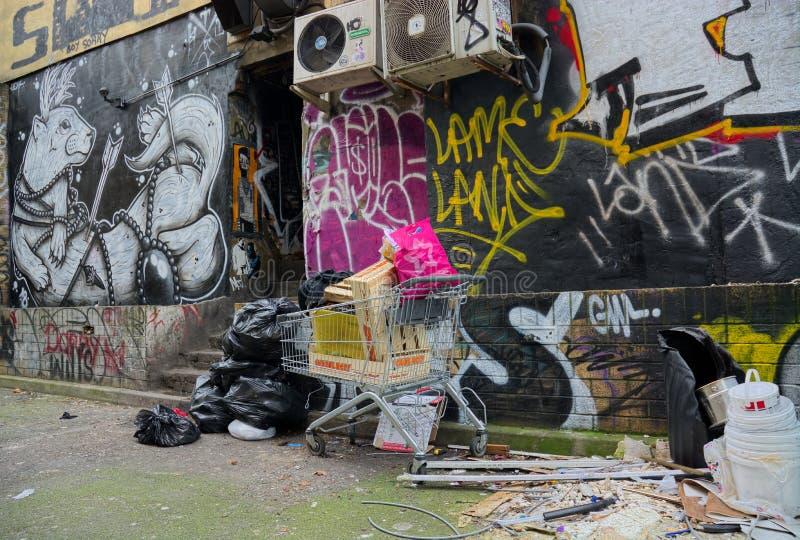 Fly Tipping Müll in Street & surreal Street Art Mural in East London stockbild