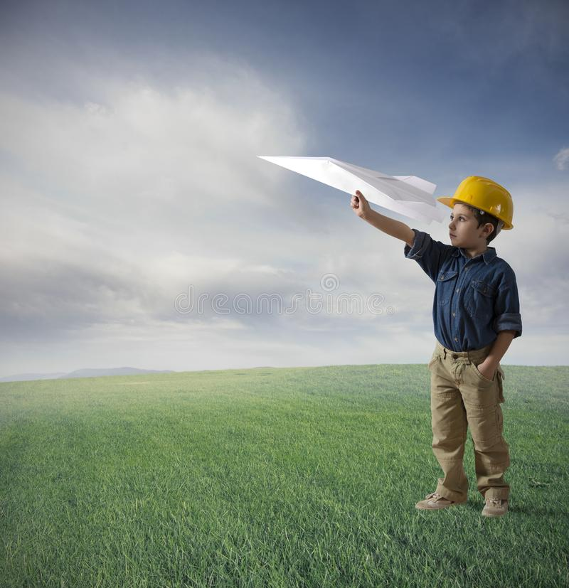 Fly. Young boy tries to fly a paper plane stock images