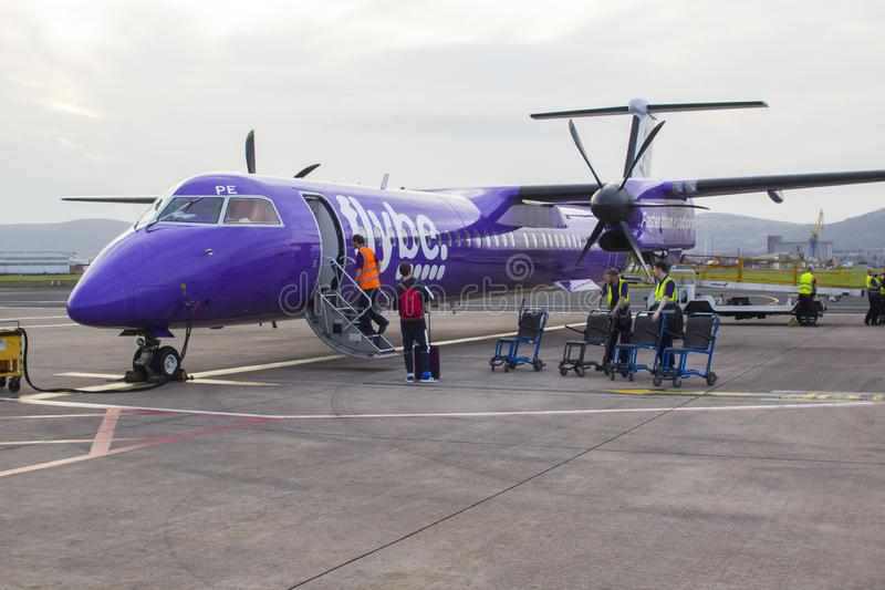 A FlyBe Dash 8 Commercial Airliner at George Best City Airport. 21 September 2019 A FlyBe Dash 8 Commercial Airliner with luggage and passenger handlers on the royalty free stock image