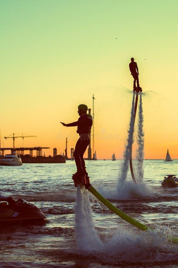 Flyboard en el cielo nocturno de St Petersburg volando y revoloteando sobre la gente del agua, en el fondo de una puesta del sol  fotos de archivo libres de regalías