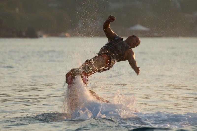 Flyboarder avec des bras tordant vers l'eau photo stock