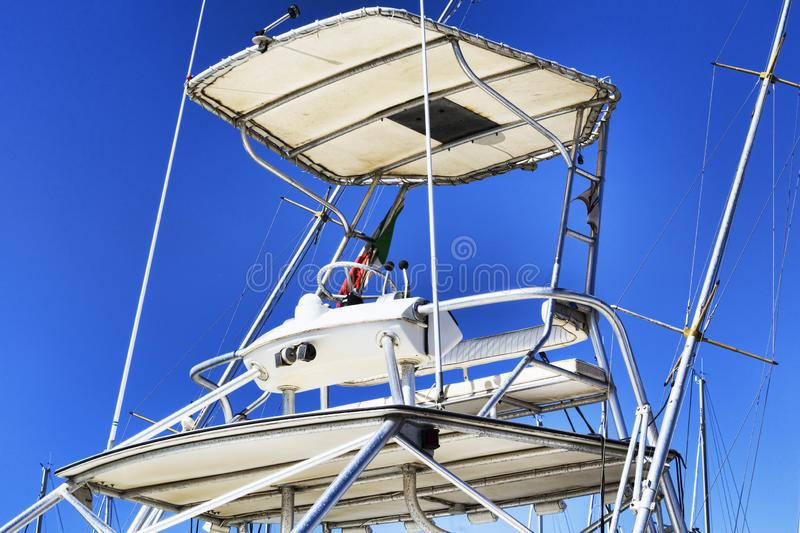 Flybridge with awning and nautical accessories of a used white boat.  royalty free stock photo