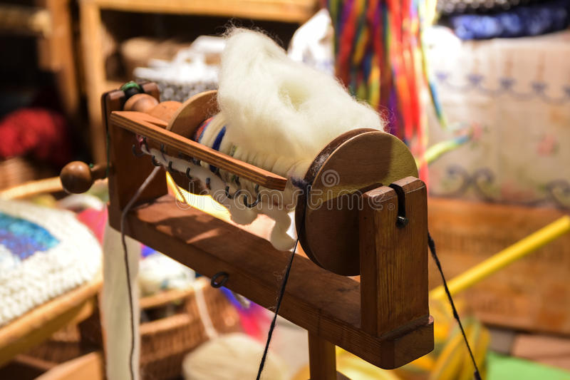 Flyer and bobbin of a wooden spinning wheel with hand-spun natural wool on an outdoor craft market stock photo