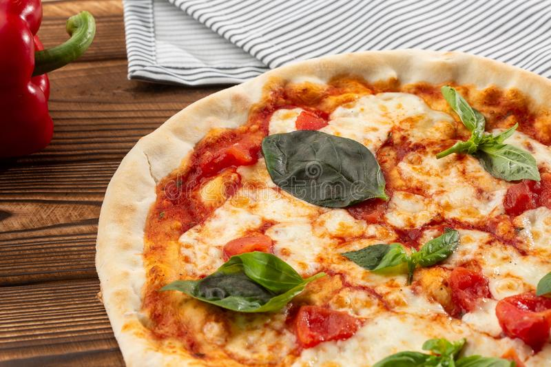 Pizza Margherita on wooden background, top view. Pizza Margarita with Tomatoes, Basil and Mozzarella Cheese close up. royalty free stock photo