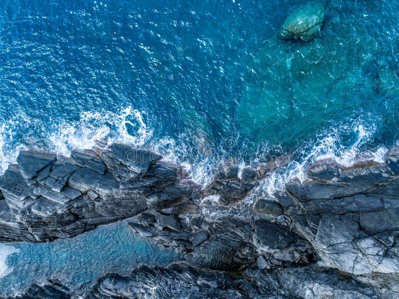 Flyg- över huvudet bästa sikt av havmedelhavvågor som når och kraschar på den steniga kuststranden, nära lopp royaltyfri fotografi