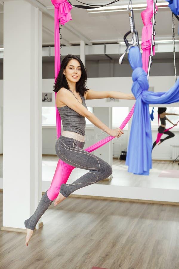 Flyg- övning eller antigravity yoga inomhus, meditation i sportidrottshall arkivfoton