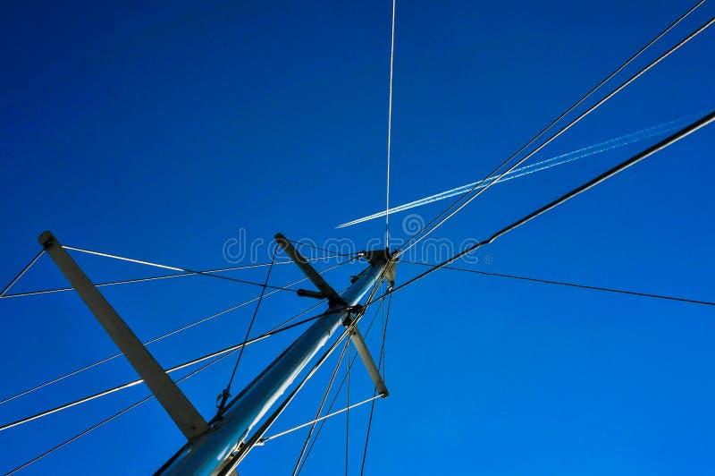 Flyg av ett flygplan i en blå himmel mot en yacht arkivbild