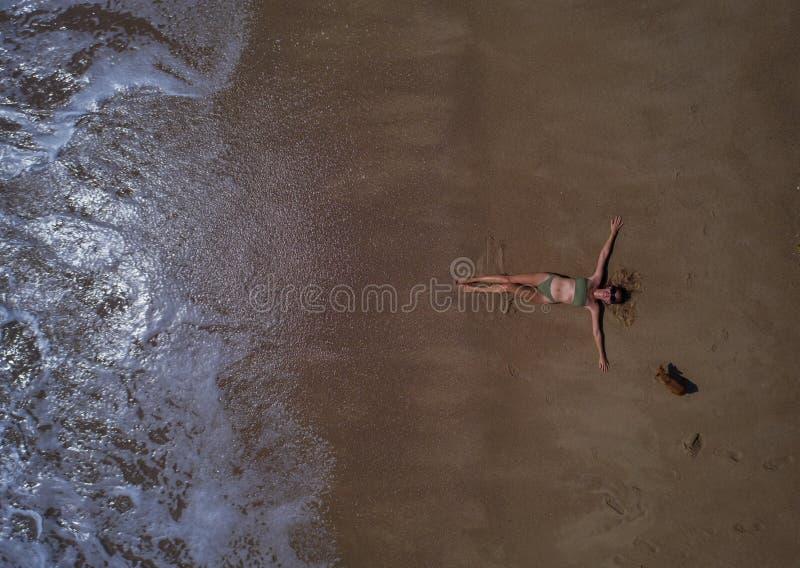 Flyg- bästa sikt av kvinnan med hennes utsträckta lägga för händer på den sandiga stranden royaltyfria foton