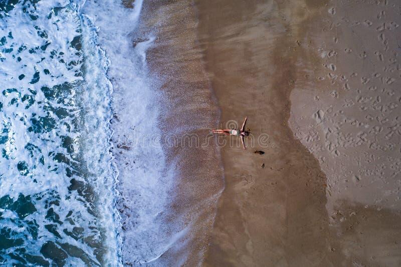 Flyg- bästa sikt av kvinnan med hennes utsträckta lägga för händer på den sandiga stranden royaltyfri foto